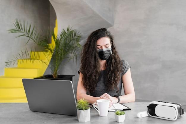 Frau, die medizinische maske drinnen trägt