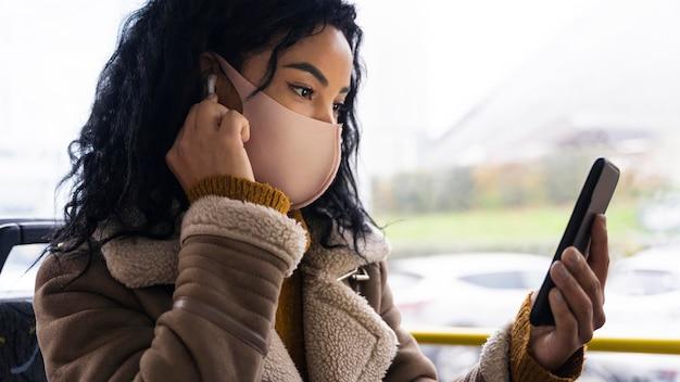 Frau, die medizinische maske im bus trägt, während musik in den ohrhörern hört