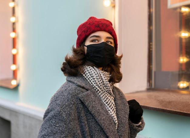 Frau, die medizinische maske in der stadt trägt