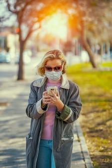 Frau, die medizinische maske in der straße in der stadt trägt und sms über smartphone schreibt