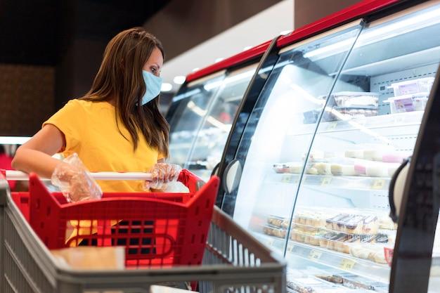 Frau, die medizinische maske trägt, die in den kühlschrank schaut