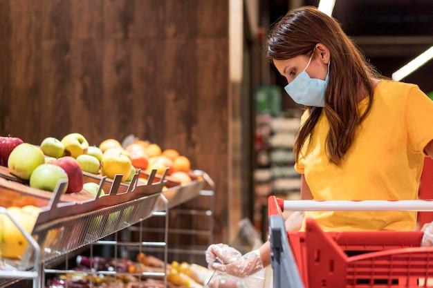 Frau, die medizinische maske trägt obst kauft