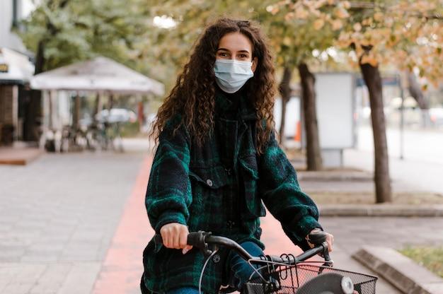 Frau, die medizinische maske trägt und die vorderansicht des fahrrads reitet