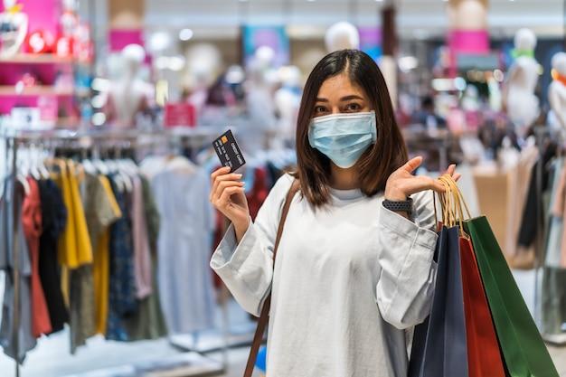 Frau, die medizinische maske trägt und kreditkarte am einkaufszentrum zur verhinderung von coronavirus hält