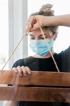 Frau, die medizinische maske trägt und mit einem plakat arbeitet