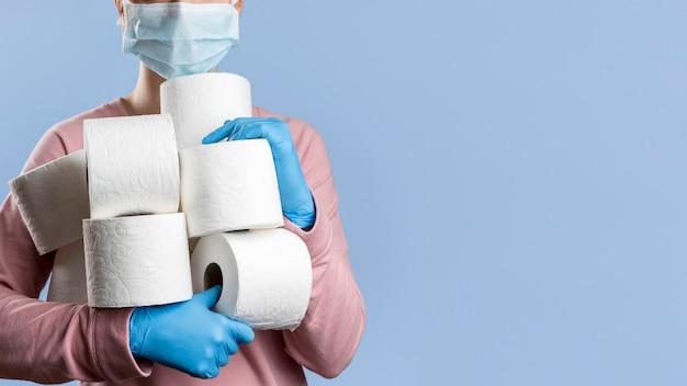 Frau, die medizinische maske und handschuhe trägt, die viele toilettenpapierrollen halten