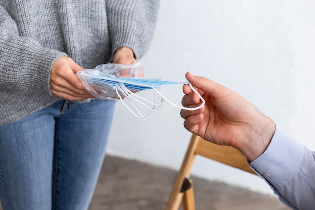 Frau, die medizinische masken an einer gruppentherapiesitzung verteilt