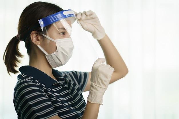 Frau, die medizinischen schutzschirm oder plastikschild auf ihrem gesicht trägt, für koronavirus oder covid-19-schutz.