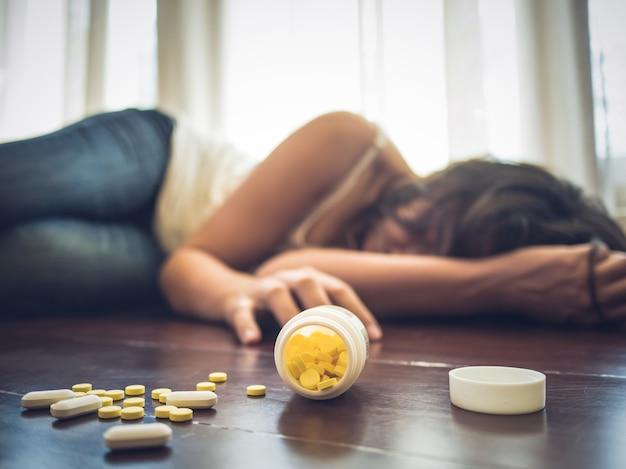 Frau, die medizinüberdosis nimmt und auf dem bretterboden liegt