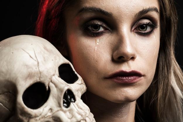 Frau, die menschlichen schädel auf schulter hält