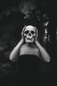 Frau, die menschlichen schädel im wald hält