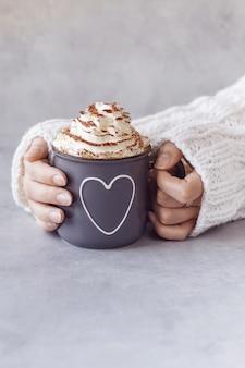Frau, die metallgrauen becher heiße schokolade mit schlagsahne in den händen hält. grauer steinhintergrund-kopienraum