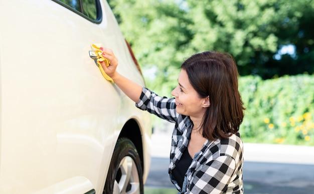 Frau, die mikrofasertuch zum abwischen des autos auf naturhintergrund verwendet
