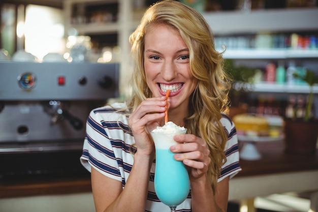 Frau, die milchshake mit einem strohhalm trinkt