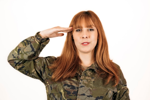 Frau, die militärische tarnung trägt, die einen militärischen handgruß mit einem lächeln gibt