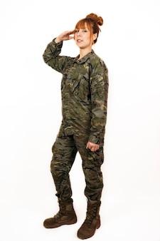 Frau, die militäruniform trägt, die einen militärischen handgruß mit einem lächeln gibt