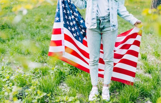Frau, die mit amerikanischer flagge steht