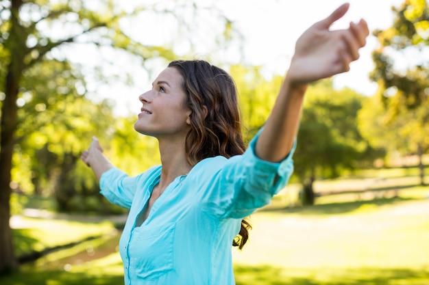 Frau, die mit ausgestreckten armen im park steht