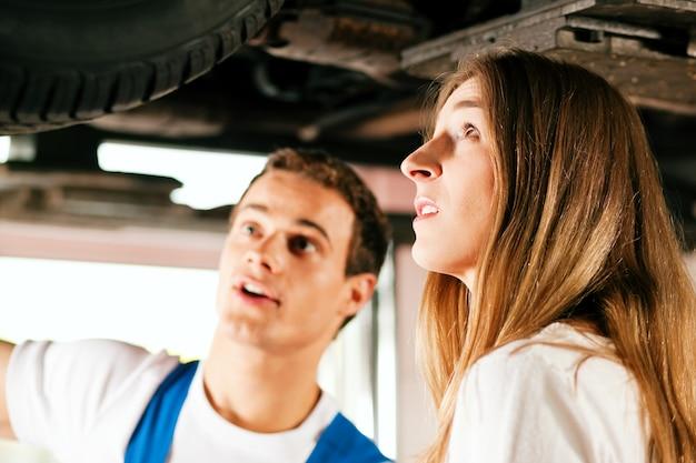 Frau, die mit automechaniker in der werkstatt spricht