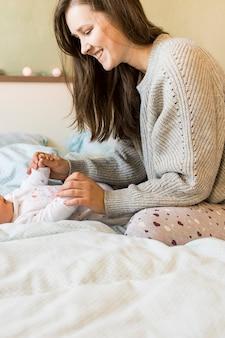 Frau, die mit baby auf bett spielt