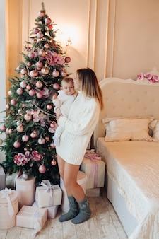 Frau, die mit baby nahe weihnachtsbaum steht.