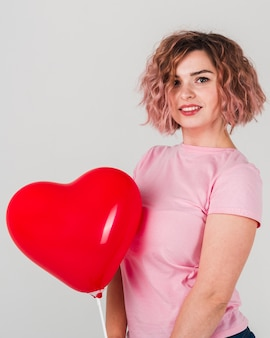 Frau, die mit ballon für valentinstag aufwirft