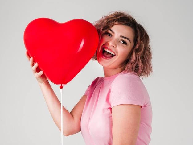 Frau, die mit ballon lächelt und aufwirft