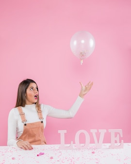 Frau, die mit ballon nahe liebesaufschrift spielt