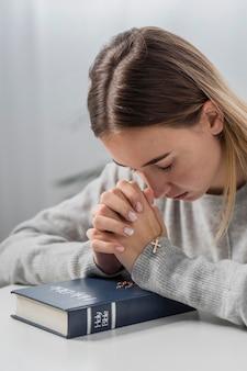 Frau, die mit bibel und kreuzkette betet