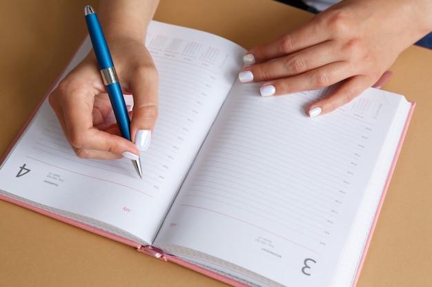 Frau, die mit blauem silbernem metallstift im rosa tagebuch schreibt