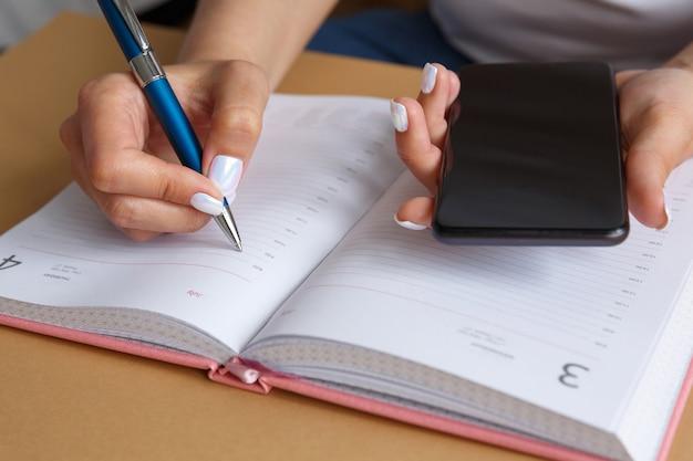 Frau, die mit blauem stift im tagebuch schreibt und smartphone in ihrer hand hält