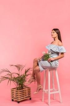 Frau, die mit blumenblumenstrauß auf stuhl sitzt