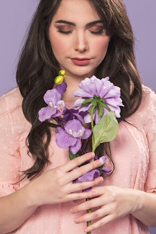 Frau, die mit blumenstrauß von orchideen und dahlie aufwirft