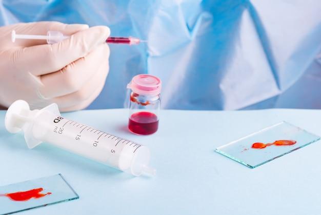 Frau, die mit blutprobe im labor, nahaufnahme arbeitet