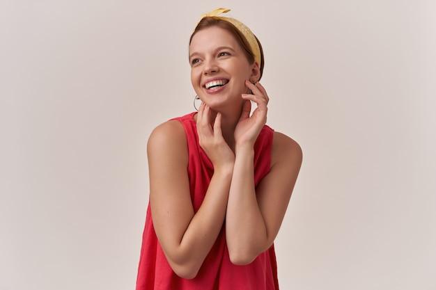 Frau, die mit braunen augen und natürlichem make-up beiseite lächelt und stilvolle rote bluse mit armen trägt, die gesichtsgefühl berühren charmantes schönes schönes lächeln, das auf weißer wand aufwirft