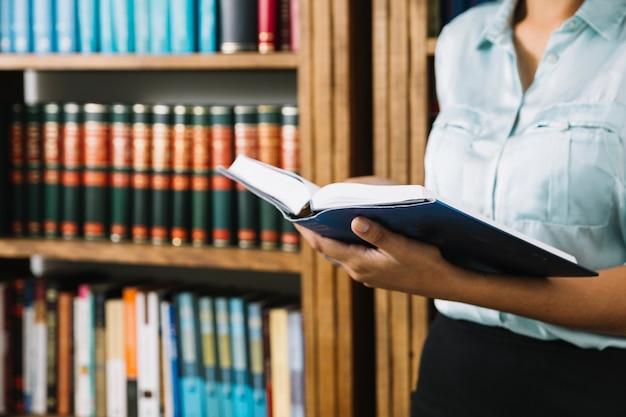 Frau, die mit buch in der bibliothek steht