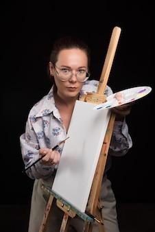 Frau, die mit bürsten und segeltuch auf schwarzem aufwirft. foto in hoher qualität