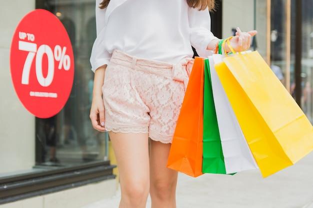 Frau, die mit bunten einkaufstaschen geht