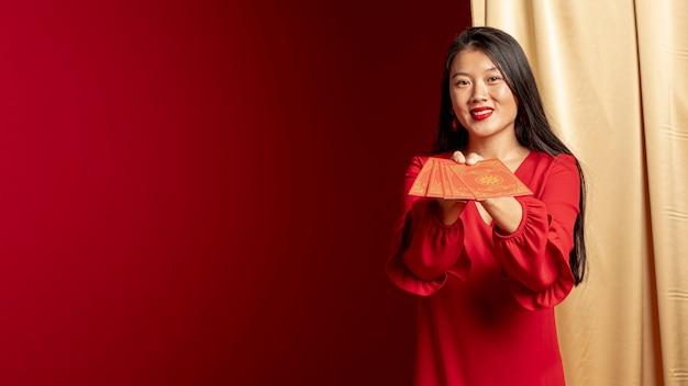 Frau, die mit chinesischen karten des neuen jahres aufwirft