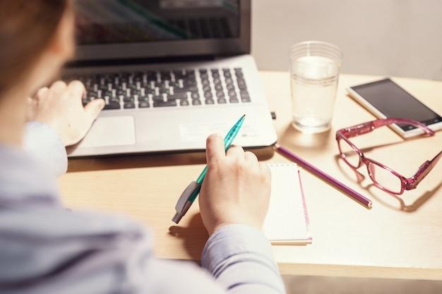 Frau, die mit computer im büro arbeitet