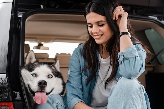 Frau, die mit dem auto mit ihrem niedlichen husky reist