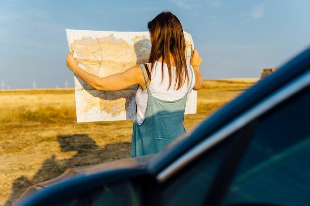 Frau, die mit dem auto reist, hat sich bei sonnenuntergang beim betrachten einer karte verloren