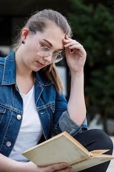 Frau, die mit dem buch sitzt im park studiert