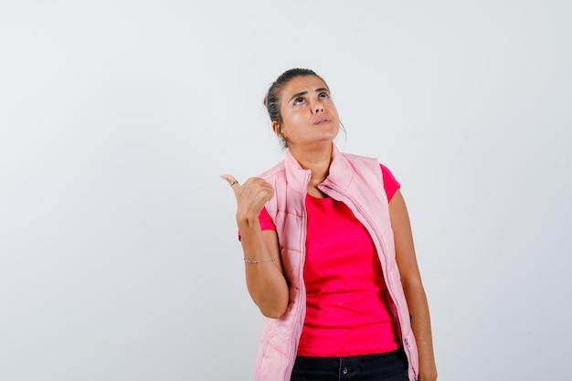 Frau, die mit dem daumen in t-shirt, weste und nachdenklichem blick nach hinten zeigt