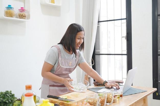 Frau, die mit dem empfang auf laptop in der küche kocht