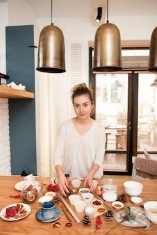 Frau, die mit dem kuchen verziert bestandteile aufwirft