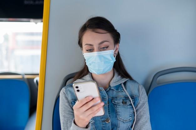 Frau, die mit dem öffentlichen bus mit dem smartphone reist, während sie eine medizinische maske zum schutz trägt