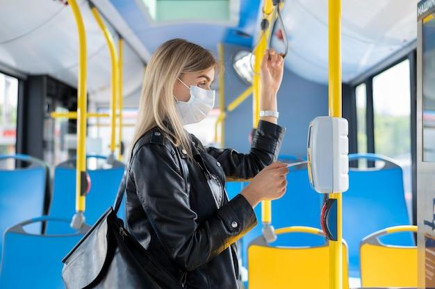 Frau, die mit dem öffentlichen bus reist, eine medizinische maske zum schutz trägt und einen buspass verwendet
