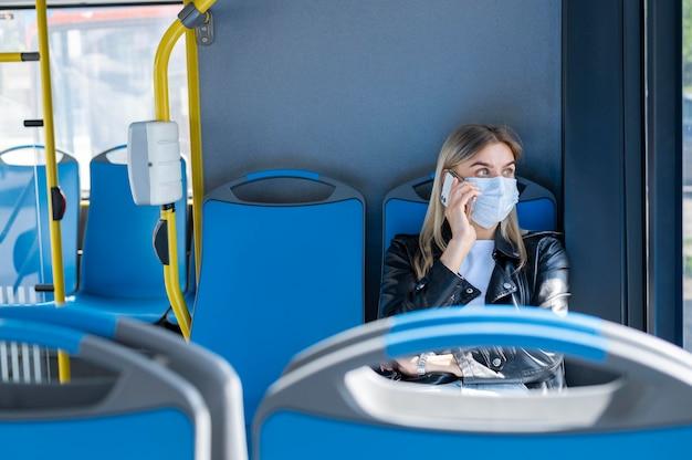Frau, die mit dem öffentlichen bus reist und telefoniert, während sie eine medizinische maske zum schutz trägt