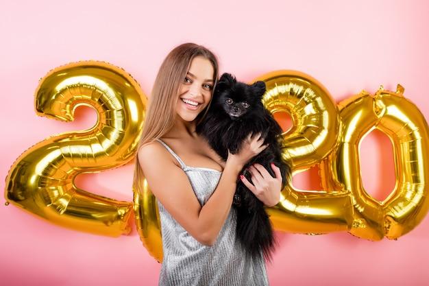 Frau, die mit dem schwarzen hund des japanischen spitzes und goldenen 2020 ballonen des neuen jahres lokalisiert über rosa lächelt